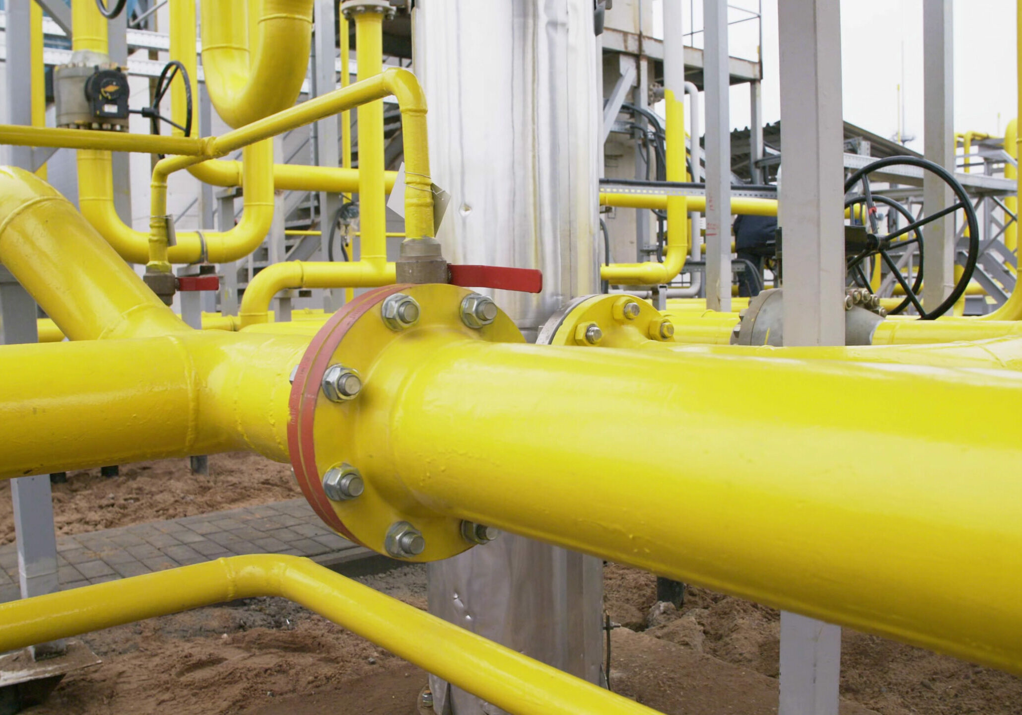 Close up of refinery plant equipment of yellow pipe line for oil and gas valves at gas plant. Heavy industry and manufacturing concept